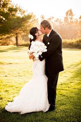 bride in mermaid gown by romona keveza kisses groom in black tux