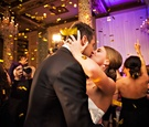 bride and groom kiss at reception while gold confetti falls around them on the dance floor