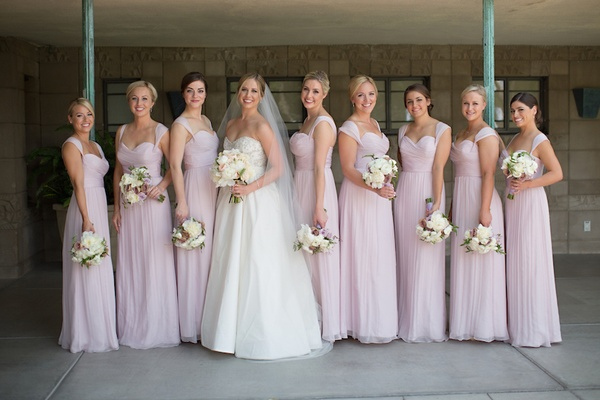 Bridesmaids in long, light purple gowns with sweetheart necklines