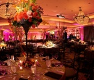 Pink lighting in reception ballroom with large flower centerpieces