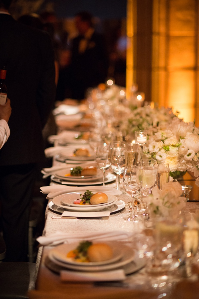 a long reception table with white china and low white floral arrangements with food