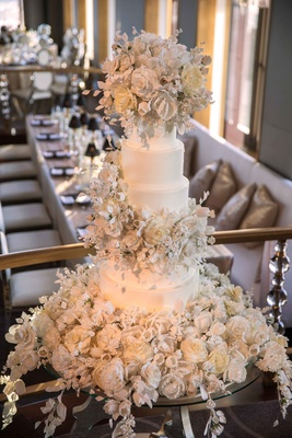 White wedding cake with hundreds of sugar flowers and leaves cascading on cake and cake table
