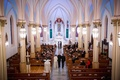 Catholic wedding ceremony with groom in black tuxedo being walked down aisle by parents, Our Lady of
