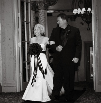 Black and white photo of bride in an Alvina Valenta gown being escorted to ceremony
