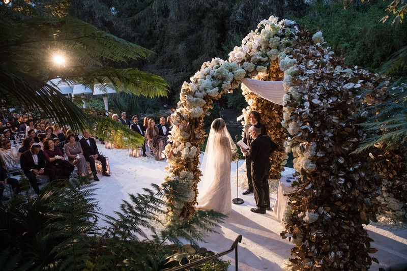 Bride in veil and wedding dress saying vows under chuppah flower in Bel-Air sunlight streaming in