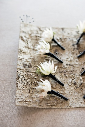 white single flower boutonnieres greenery black fabric wrapped around pins