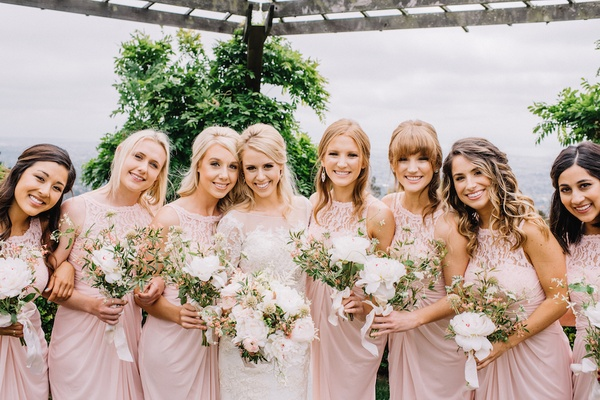 Bride with seven bridesmaids in light pink bridesmaid dresses