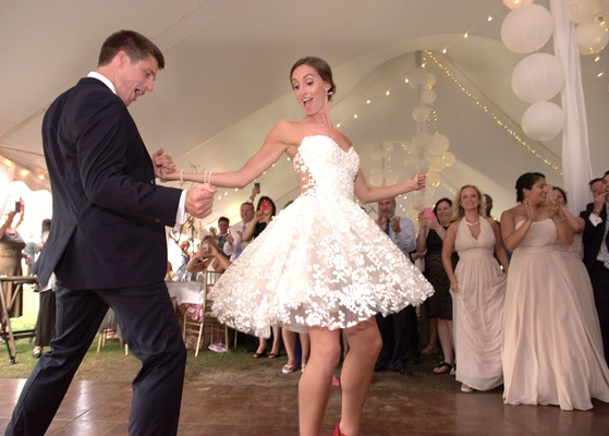 Bride twirls in Mark Zunino for Kleinfeld short wedding dress with flower embellishments sheer back