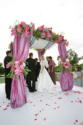Jewish bride and groom under vibrant chuppah