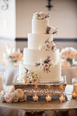 White wedding cake ribbed frosting buttercream with clusters of fresh ranunculus rose purple foliage