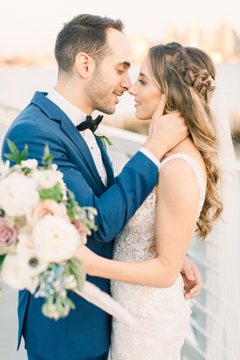 groom in teal suit preparing to kiss bride in lace dress with braided crown