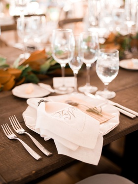 Wood table with no linens place setting white plate linen napkin monogram magnolia leaf garland