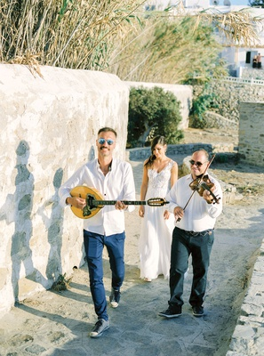 mykonos greece destination wedding ceremony processional bouzoukia musicians walking bride to church