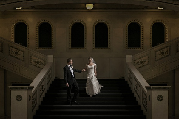 James thoughtfully led Jen down the stairs of the Chicago Cultural Center after their wedding.