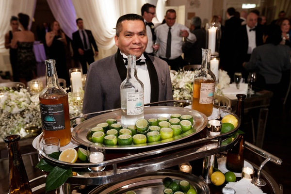 server with cart filled with hollowed out lime shot glasses and casamigos tequila