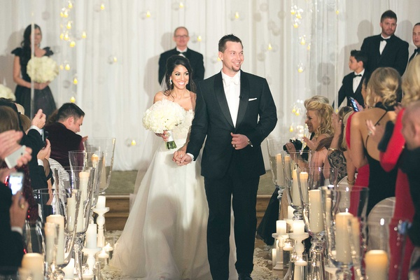 Bride in Heidi Elnora wedding dress with groom in tuxedo walking up white aisle runner candles