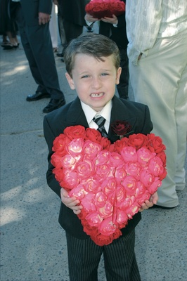 Ring bearer holding red and pink heart shaped ring pillow