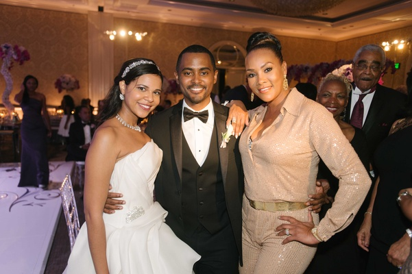 Bride and groom with Vivica A Fox wearing tan collared jumpsuit to wedding