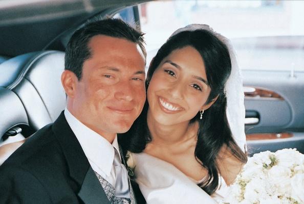 Bride and groom smile inside wedding transportation