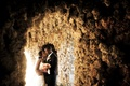 Bride and groom kiss inside cave in Miami