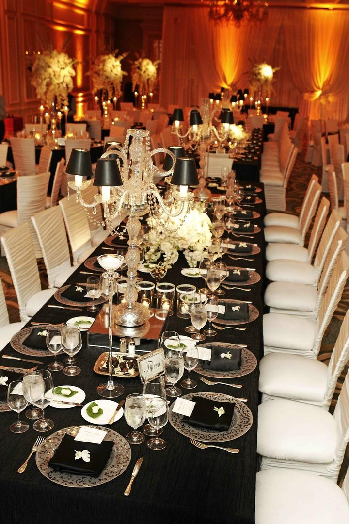 Long wedding table with black tablecloth and white chairs