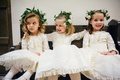 Cute flower girls sitting on bench ivory vintage antique flower girl dresses and flower crowns