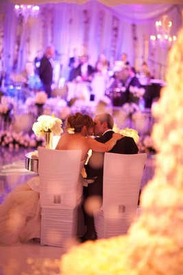 Bride and groom kiss at sweetheart table during reception