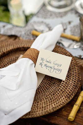 Wedding reception place setting with rattan charger and napkin ring, calligraphy place card