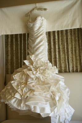 White wedding dress on hanger in hotel room