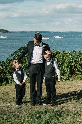 groom posing two ring bearers little tuxedos bow ties green black white maine atlantic ocean peaks