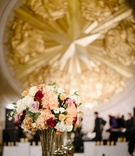 Mercury glass centerpiece with light peach hydrangeas, red roses, pink roses, white hydrangeas gold