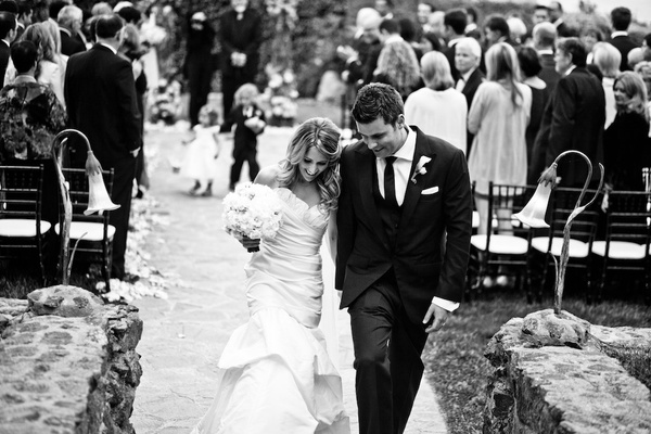Black and white photo of bride and groom leaving ceremony