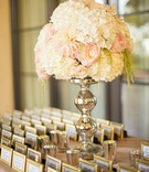 Gold frame escort cards with white and blush flower arrangement