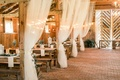 Wood wedding reception barn white sheer drapery brick floor wood picnic tables greenery lantern