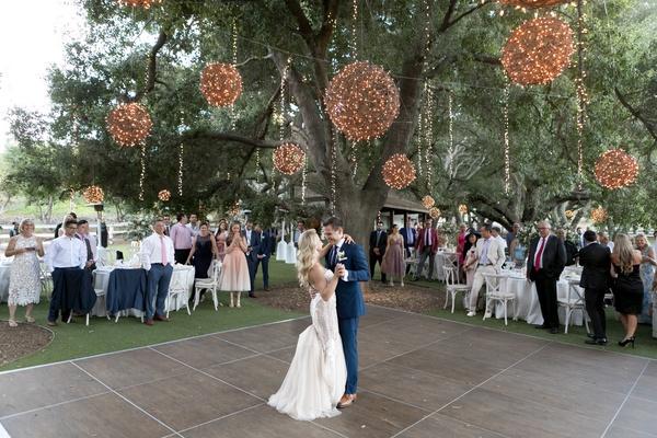 saddlerock ranch wedding outdoor reception, wooden outdoor dance floor, first dance twinkle lights