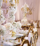 wedding reception s shape serpentine table tall centerpiece white flowers gold candelabra chairs