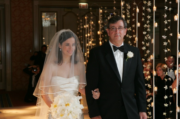 Bride in a veil and strapless gown and father of the bride in a black tuxedo
