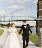 bride in strapless sweetheart watters wedding dress, groom in michael kors tux, bridge