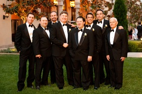 Groom and his seven groomsmen in black tuxedos
