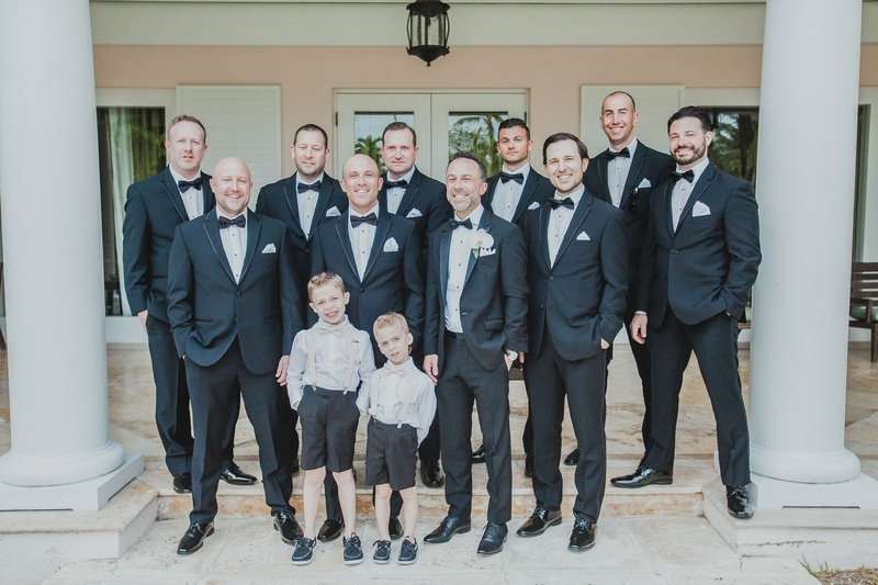 groom and groomsmen in black suits with ring bearers in shorts