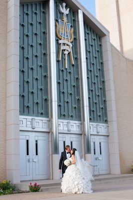 Bride in ruffle wedding dress kisses tux groom in front of church