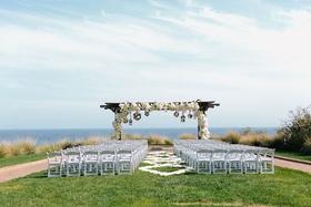 oceanfront wedding ceremony overlooking the pacific ocean wooden arch white flowers mirror balls