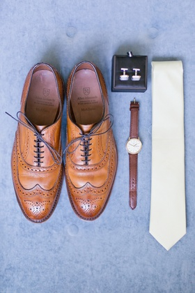 Groom's tan wing-tip shoes, watch with brown band, cuff links, and pastel yellow tie