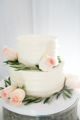 simple two-tier wedding with white frosting, pale blush roses, greenery