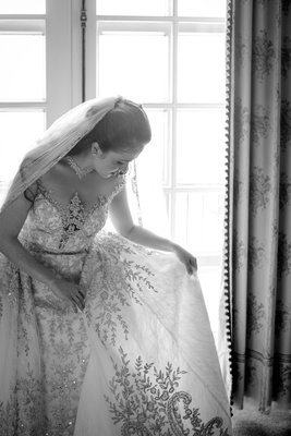 Black and White Photo of bride looking at detail of wedding dress from Kleinfeld Bridal beading