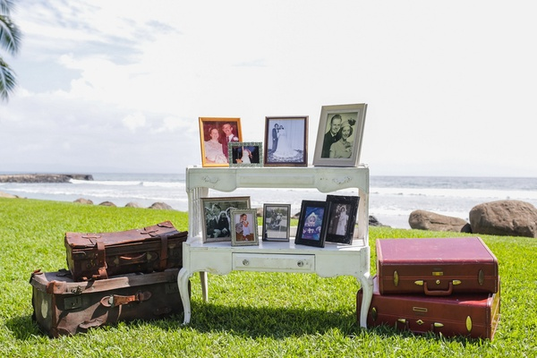 old family photos displayed with vintage suitcases at travel themed maui wedding outdoor