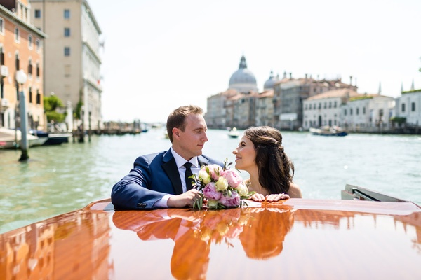 Bride and groom with bouquet on back of wooden boat italy wedding elopement destination