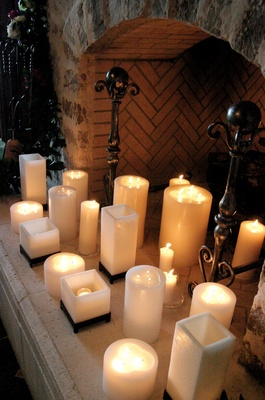 Lit candles in a fireplace of a wedding reception
