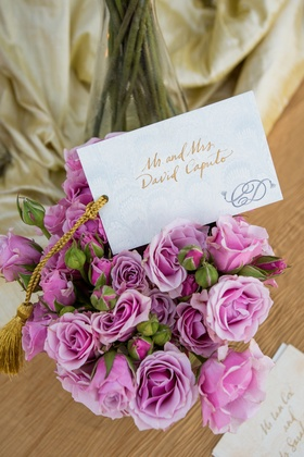 Bouquet of light purple roses with a card with gold script and couple's monogram