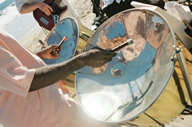Musicians perform steel drum and guitar music on beach